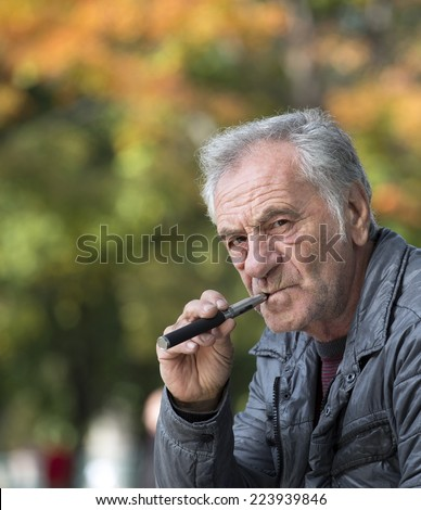confident old man smoking an electronic cigarette - stock photo