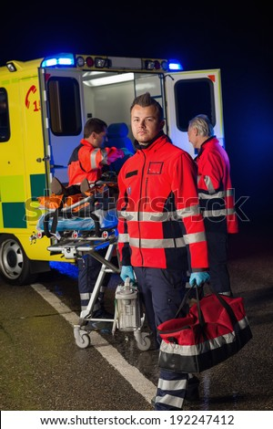Confident paramedic with team assisting injured patient during road accident - stock photo