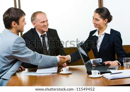 Confident partners sitting at the table and shaking hands - stock photo