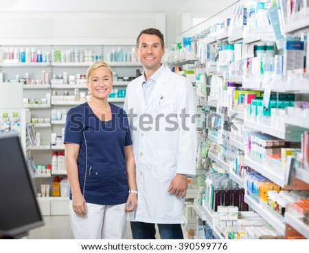 Confident Pharmacist And Assistant Standing In Pharmacy - stock photo