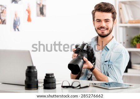 COnfident photographer. Cheerful young man holding digital camera and smiling while sitting at his working place - stock photo