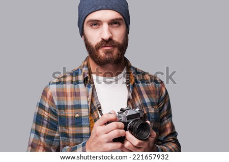 Confident photographer. Handsome young bearded man holding old-fashioned camera and looking at camera while standing against grey background - stock photo