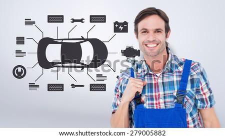 Confident plumber holding tool over white background against grey vignette - stock photo