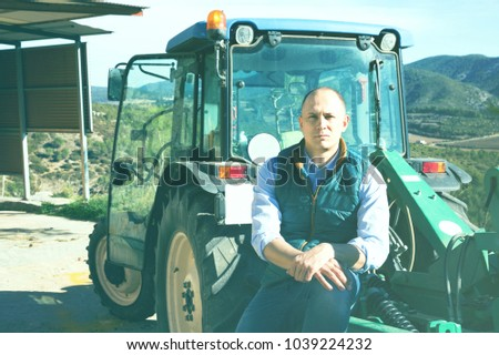 Confident  positive smiling male owner of vineyard posing near tractor outdoors in sunny day