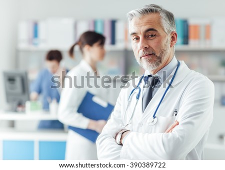 Confident professional doctor posing in the office with crossed arms and looking at camera - stock photo