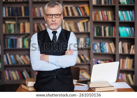 Confident professor. Confident grey hair senior man in formalwear keeping arms crossed and looking at camera while leaning at the table and with bookshelf in the background - stock photo