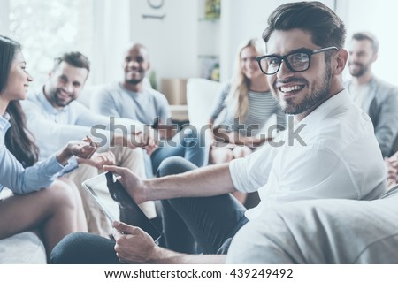 Confident psychologist. Group of young cheerful people sitting in circle and discussing something while young man holding digital tablet and looking over shoulder with smile - stock photo