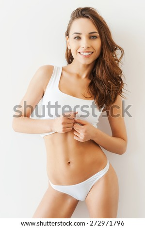 Confident pure beauty. Attractive young woman in white tank top and panties posing while standing against white background - stock photo