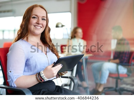 Confident redhead female designer working on a digital tablet in red creative office space