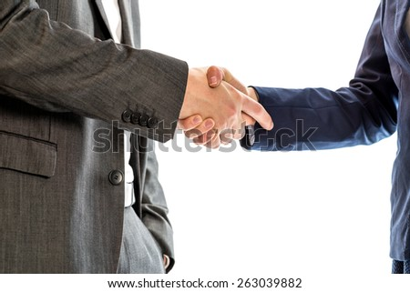 Confident relaxed businessman with his hand in his suit pocket shaking hands with  businesswoman to conclude a deal, agreement, partnership or in congratulations. - stock photo