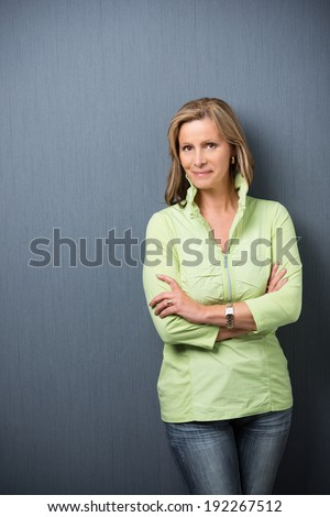 Confident relaxed trendy middle-aged woman leaning against a grey background with folded arms smiling at the camera - stock photo