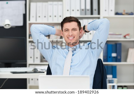 Confident relaxed young businessman sitting back in his chair at the office with his hands clasped behind his head smiling at the camera - stock photo
