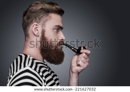 Confident sailor. Side view of confident young bearded man in striped clothing smoking a pipe and looking away while standing against grey background