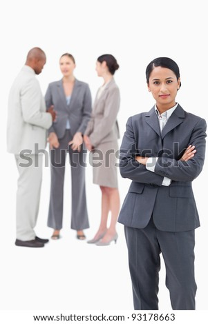 confident saleswoman with negotiating trading partners behind her against a white background