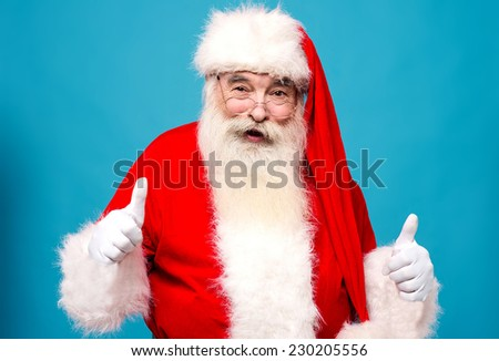 Confident santa claus showing thumbs up - stock photo