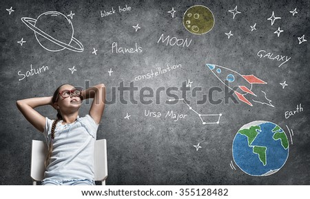 Confident school girl with hands on head sitting at desk - stock photo