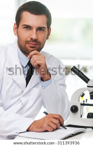 Confident scientist. Handsome young scientist in white uniform holding hand on chin and writing in note pad while sitting at his working place - stock photo