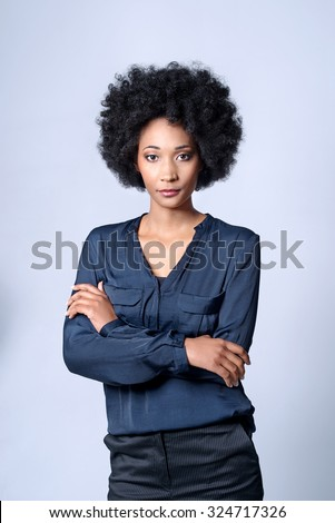 Confident self assured black african business woman with afro in studio, isolated on grey background - stock photo