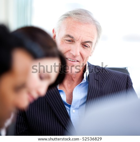 Confident senior businessman in a meeting with his team - stock photo