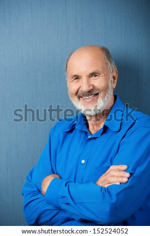 Confident senior man with folded arms standing against a green blackboard smiling at the camera - stock photo