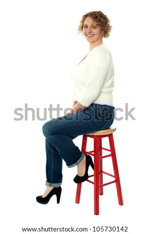Confident senior woman looking at you as she rests on stool, studio shot