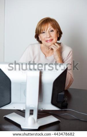 Confident Senior Woman Using Computer In Class - stock photo