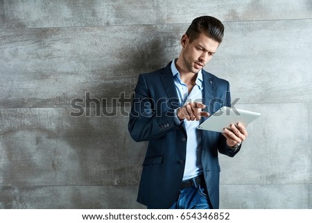 Confident serious businessman using tablet at office.