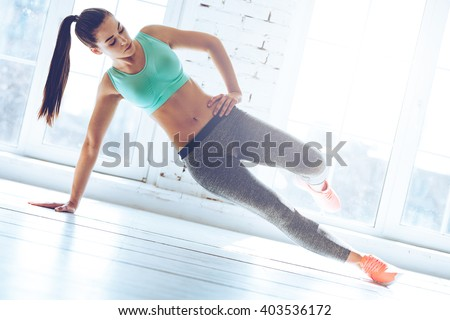 Confident side plank. Full length of young beautiful woman in sportswear doing side plank in front of window at gym  - stock photo