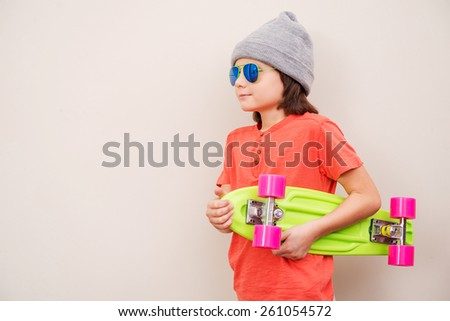Confident skater. Side view of confident little boy in hat holding colorful skateboard while standing against grey background - stock photo