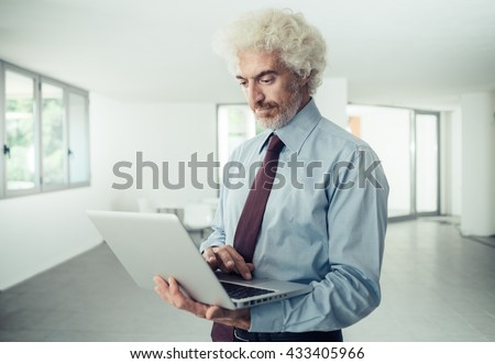 Confident smiling businessman holding a laptop and typing, he is standing in the office, interior on background