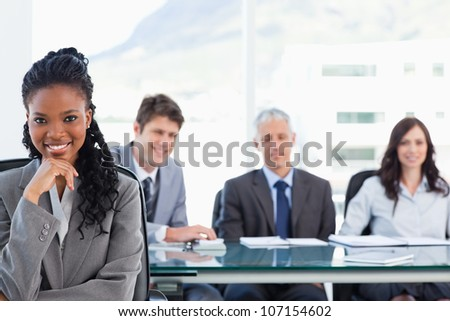 Confident smiling executive sitting in a meeting room while her team is looking at her