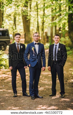 Confident smiling handsome groom in black suit with two groomsman in pine wooden park