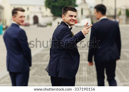 Confident smiling handsome groom in black suit with two groomsman in the city