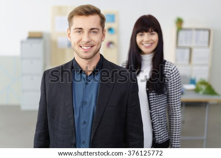 Confident smiling manager or team leader standing in the office looking at the camera with an attractive female colleague in the background - stock photo