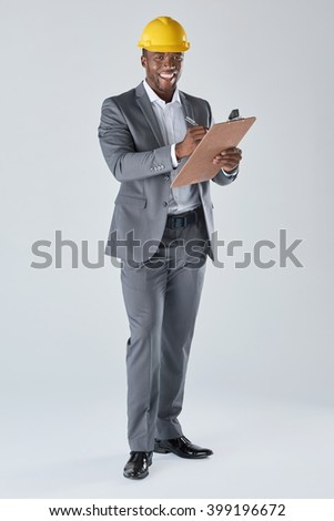 Confident smiling portrait of black architect engineer designer with construction hardhat in business suit isolated in studio - stock photo