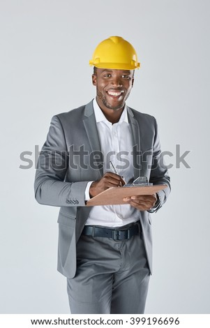Confident smiling portrait of black engineer construction surveyor with hardhat isolated in studio