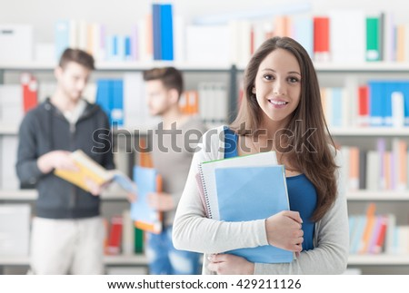 Confident smiling student girl posing in the library, holding notebooks and looking at camera, learning and education concept - stock photo