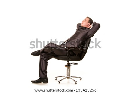 Confident smiling young businessman relaxing on a chair isolated on white - stock photo