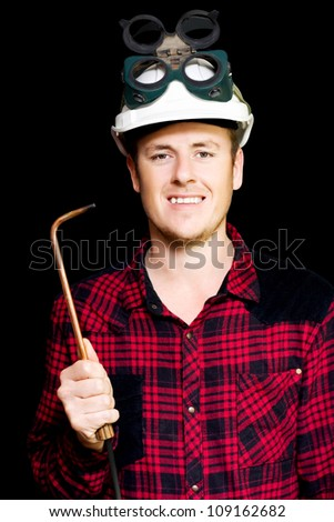 Confident smiling young panel beater wearing a safety helmet and goggles and holding an welding torch in hand on a black studio background - stock photo