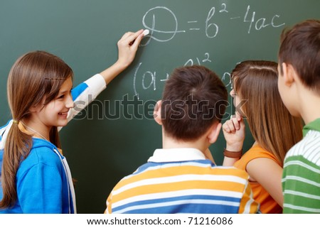 Confident student explaining formula on blackboard during algebra lesson - stock photo