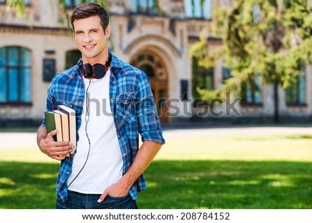 Confident student. Handsome young man holding books and smiling while standing in front of his university - stock photo