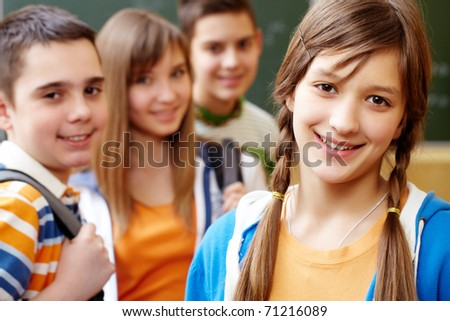 Confident student looking at camera with her friends behind