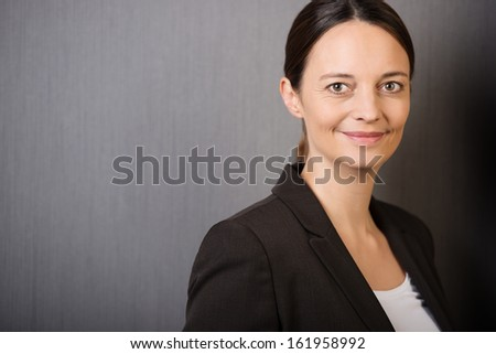 Confident stylish businesswoman with a warm friendly smile, head and shoulders portrait on grey - stock photo