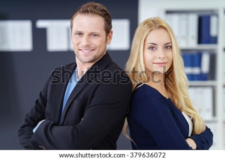 Confident successful business team of a man and woman standing back to back in the office with folded arms smiling at the camera - stock photo