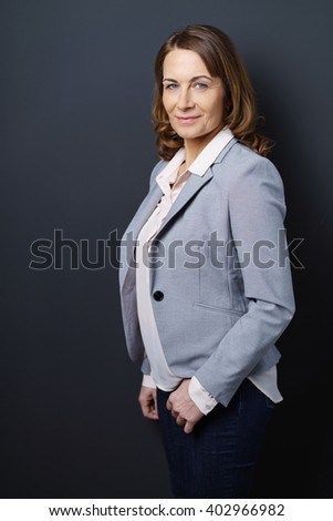 Confident successful businesswoman or entrepreneur standing sideways with her hand in her pocket turning to smile at the camera, three-quarter pose - stock photo