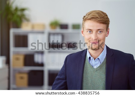Confident successful young businessman posing in the office looking at the camera with a warm friendly smile - stock photo