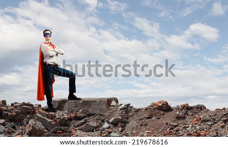 Confident superhero in cape and mask standing on ruins - stock photo