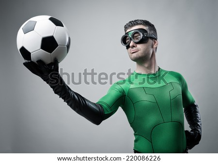 Confident superhero in green costume holding a soccer ball. - stock photo