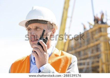 Confident supervisor using walkie-talkie at construction site - stock photo