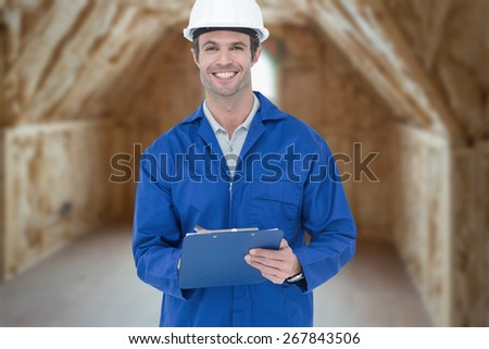 Confident supervisor writing notes against room in house under construction - stock photo
